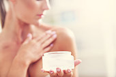 Picture showing fit woman holding lotion over her body