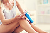Picture showing fit woman holding lotion over her legs