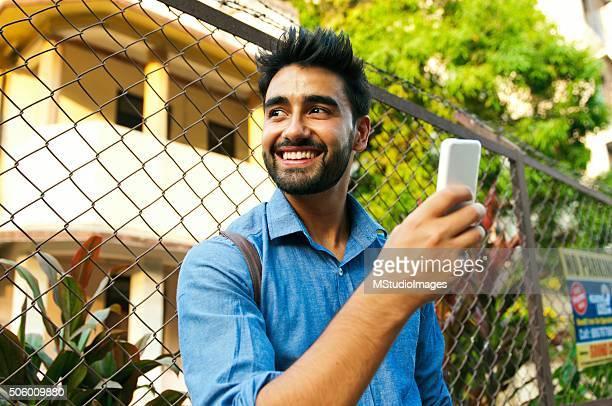 Portrait de bel homme souriant à l'aide de son smartphone