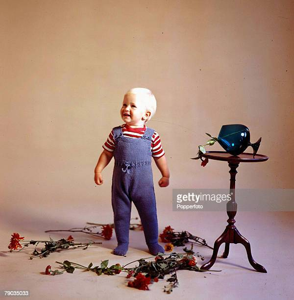 1964 A picture of a happy baby boy who is dressed smartly in a red and white top and blue woollen dungarees He is standing in a studio next to a...