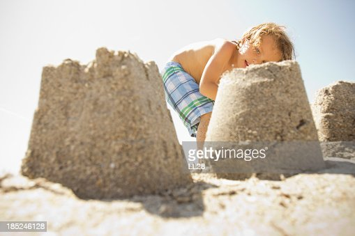 A picture of a little boy looking at a sand castle