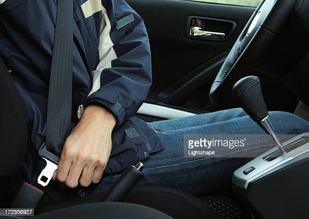 A picture of a man buckling his seat belt