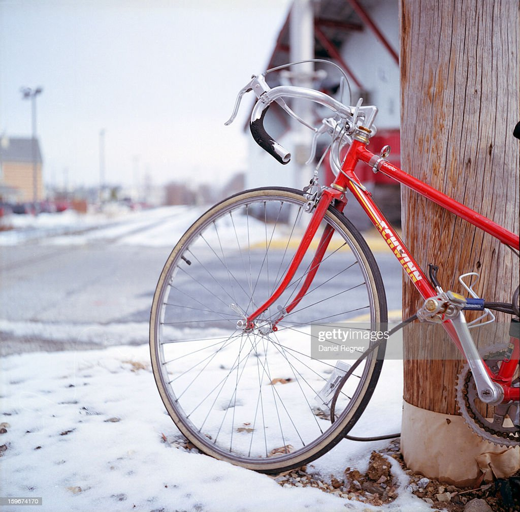 CONTENT] A picture of a red Schwinn bicycle, locked up against a pole on wintry streets in the snow. The bike looks brand new, shiny and red, and has chrome handlebars. Bicycling in harsh weather.