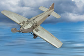 Picture of a retro gray metal toy airplane. In the background, blue sky with clouds and sea.