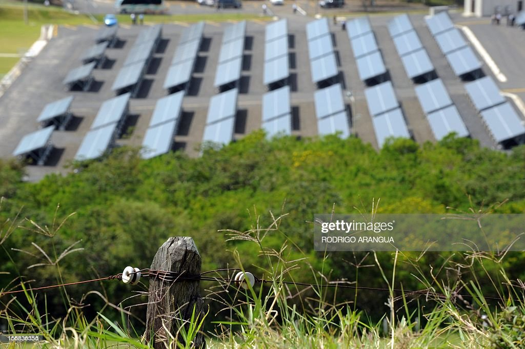 Picture of a rusty wire fence seen near the Miravalles Solar Power Plant (background) in Miravalles, 220 km north of San Jose, taken on November 22, 2012. Costa Rica inaugurated the largest plant of electricity from solar energy in Central America, which may generate 1.2 gigawats a year and was built with funds from the Japanese government. AFP PHOTO/Rodrigo ARANGUA