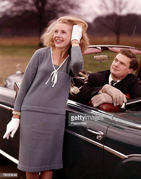 1961 A picture of a smiling female model wearing a grey outfit with white accessories being watched by a man in a black suit and tie sitting in his...
