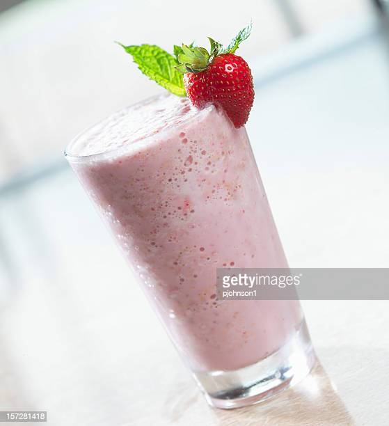 A picture of a strawberry shake with a strawberry