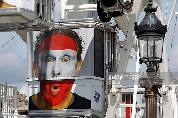 A picture of a supporter with the Austrian flag painted on his face is displayed on a nacelle of the ferris wheel on Place de la Concorde on April 28...