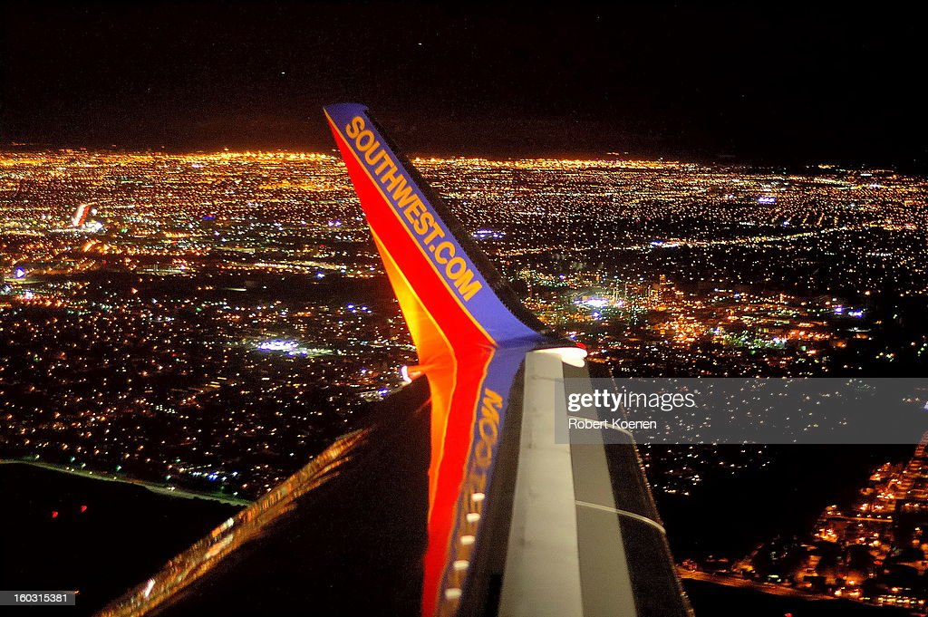 CONTENT] Picture of a wingtip of a Southwest airplane, in flight over Los Angeles. It's night, and the LA city lights can be seen extending towards the horizon. The picture was shot from the plane cabin, from a window seat over the wing. The wingtip is brightly lit