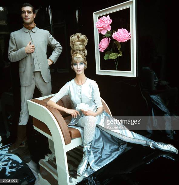 1965 A picture of a woman wearing a flamboyant fulllength shiny outfit sitting smiling at the camera within an artistic room with another smartly...