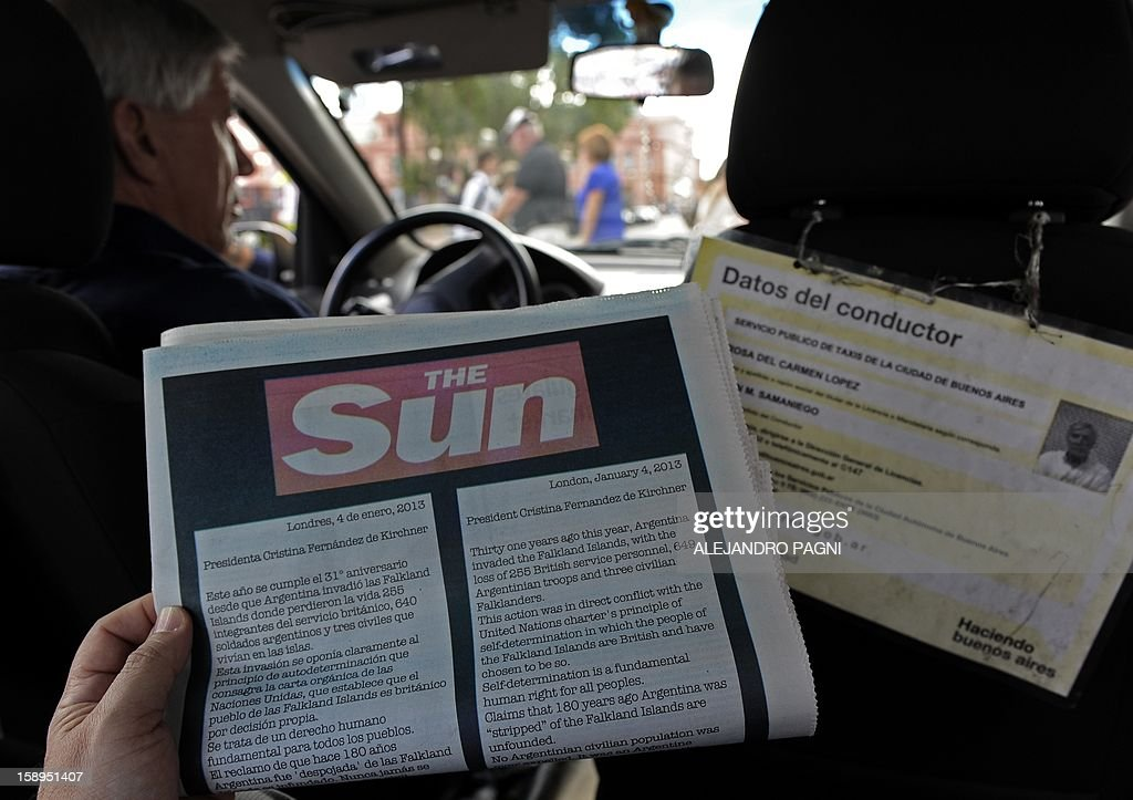 Picture of an advert placed in the Buenos Aires Herald by Britain's biggest-selling tabloid The Sun warning Argentina to keep its 'hands off' the Falklands, taken as a cab driver passes near the presidential palace Casa Rosada (background) in Buenos Aires, on January 4, 2013. The Sun hit back at Argentina's President Cristina Fernandez de Kirchner's renewed claim over the disputed Falkland Islands in an open letter to her in the Buenos Aires Herald newspaper on Friday, a day after Fernandez de Kirchner published her own open letter in two British newspapers urging Britain to give up the South Atlantic islands. AFP PHOTO/ALEJANDRO PAGNI