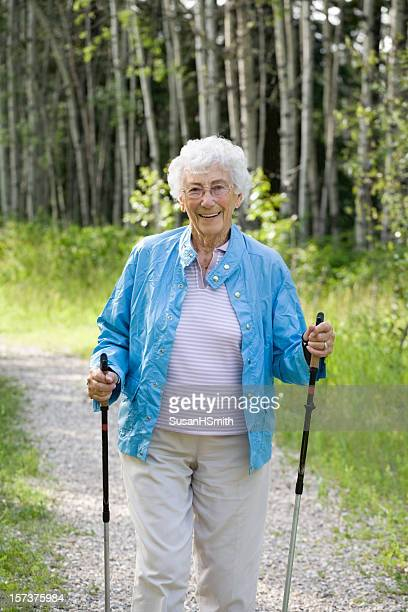 A picture of an older woman walking in the woods