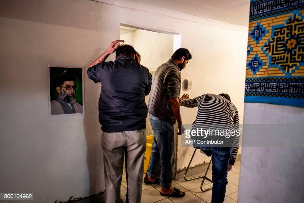 A picture of current Supreme Leader of Iran Ali Hussein Khamenei hangs on a wall as worshippers perform ritual ablutions at the Islamic Centre for...