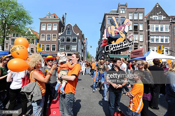 A picture of Dutch Princess Maxima hangs on the facade of the Barking Fish Cafe in Amsterdam as people celebrate Queens day below on April 30 2011...