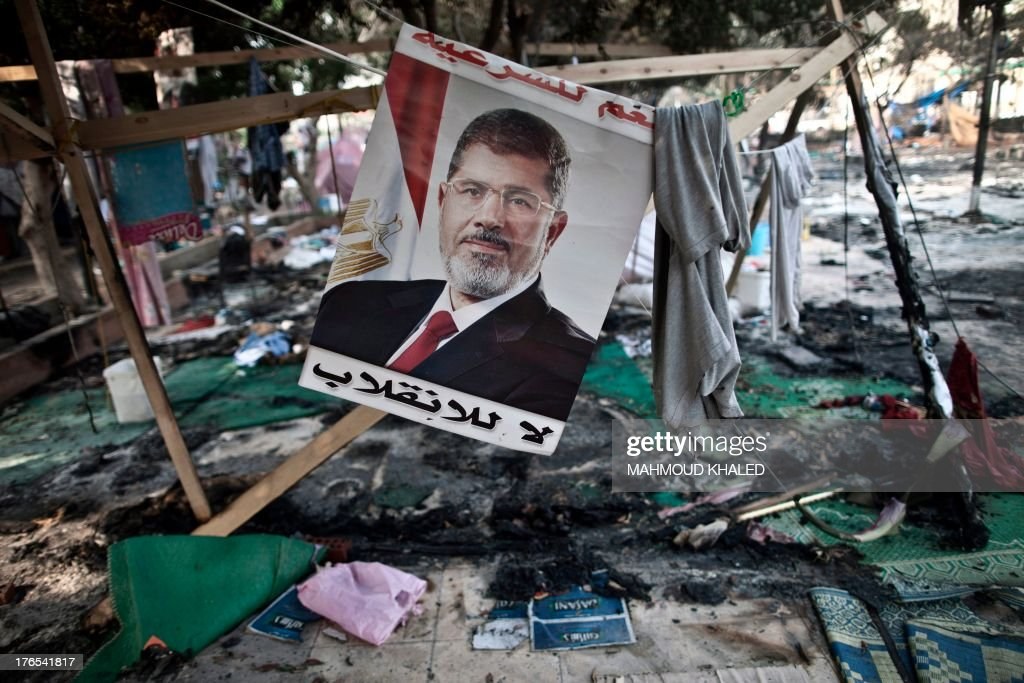A picture of Egypt's ousted president Mohamed Morsi is seen hanging admist debris at Rabaa alAdawiya square in Cairo on August 15 following a...