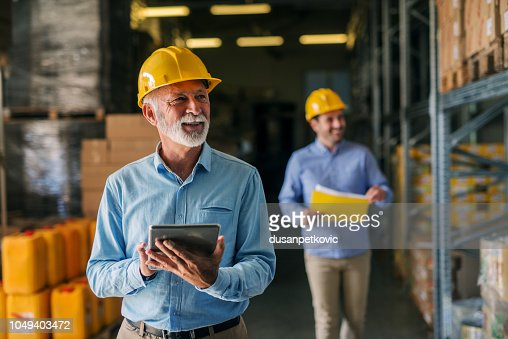Picture of father and son walking through their warehouse with helmets on their heads. Father is holding digital tablet in his hand and looking at shelf full of boxes with smile on his face. : Stock Photo