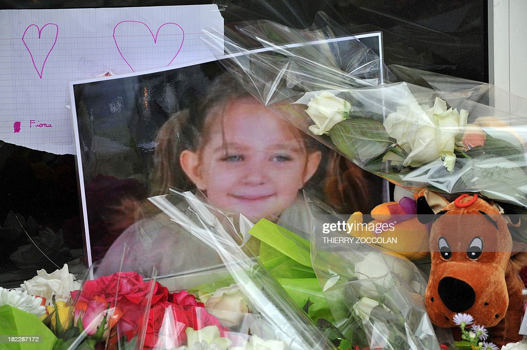 A picture of five-year-old Fiona lies among flowers, toys and messages left outside the house where she used to live in Clermont-Ferrand on September 29, 2013. French police are still searching for the body of Fiona whose mother, who was taken into questioning with her partner, admitted to investigators that the girl had died and her body was at the edge of a forest. AFP PHOTO/THIERRY ZOCCOLAN