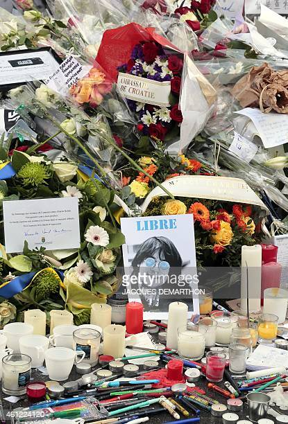 A picture of French late cartoonist Jean Cabut aka Cabu flowers candles and pens are placed at the entrance of the French weekly newspaper Charlie...