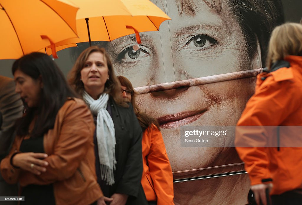 A picture of German Chancellor and Chairwoman of the German Christian Democrats (CDU) Angela Merkel displayed on the side of a CDU election campaign bus peeks through among CDU campaign workers outside CDU headquarters on September 16, 2013 in Berlin, Germany. Germany faces federal elections on September 22 and so far the CDU has a strong lead in polls over the opposition.