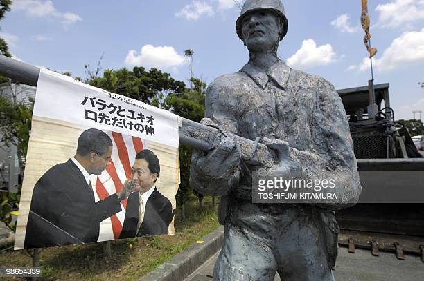 A picture of Japanese Prime Minister Yukio Hatoyama and US President Barack Obama is displayed hanging on the statue 'Bayonets and Bulldozers' used...
