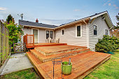 Picture of Large wooden back deck with two chairs. House exterior.