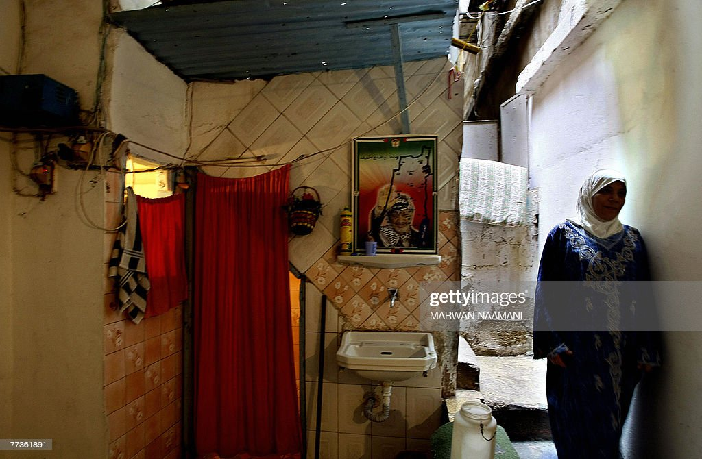 A picture of late Palestinian leader Yasser Arafat sits above a sink next to an orange curtain which replaces the door of a shower, in a makeshift bathroom inside a home in the refugee camp of Burj al-Barajneh in Beirut, 17 October 2007. Human rights group Amnesty International issued a damning report on the living conditions of Palestinian refugees in Lebanon and urged the government in Beirut to act to end their suffering. 'They live in dark, sunless, cramped conditions with almost no hope of improving their daily life or returning to Palestine, their country of origin,' Mein Sammonds, co-author of the report, told AFP.