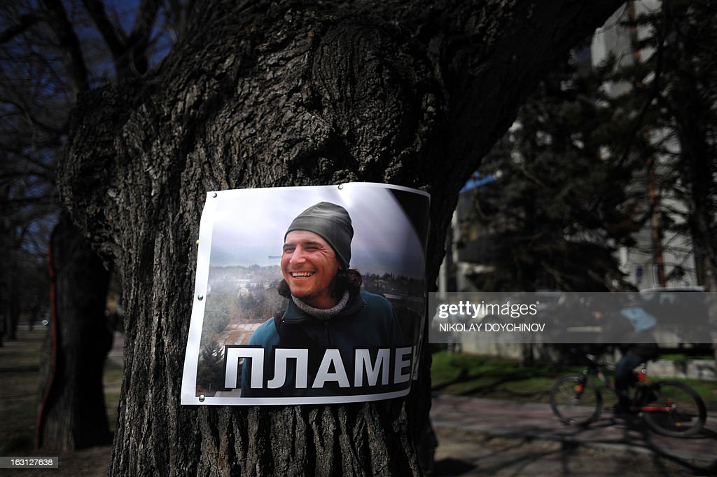 A picture of Plamen Goranov is pinned on a tree on March 5, 2013 in Varna, next to the site where he set himself on fire, and became a symbol of the three-week wave of protests against corruption. Plamen Goranov, a 36-year-old amateur photographer and rock climber, died the day before after setting himself ablaze on February 20 in the Black Sea city of Varna. Goranov's self-immolation prompted Varna protestors to adopt his cause and turn their initial anger over high electricity bills against the long-time mayor, whom they accused of corruption and favouritism towards a local business group. AFP PHOTO / NIKOLAY DOYCHINOV