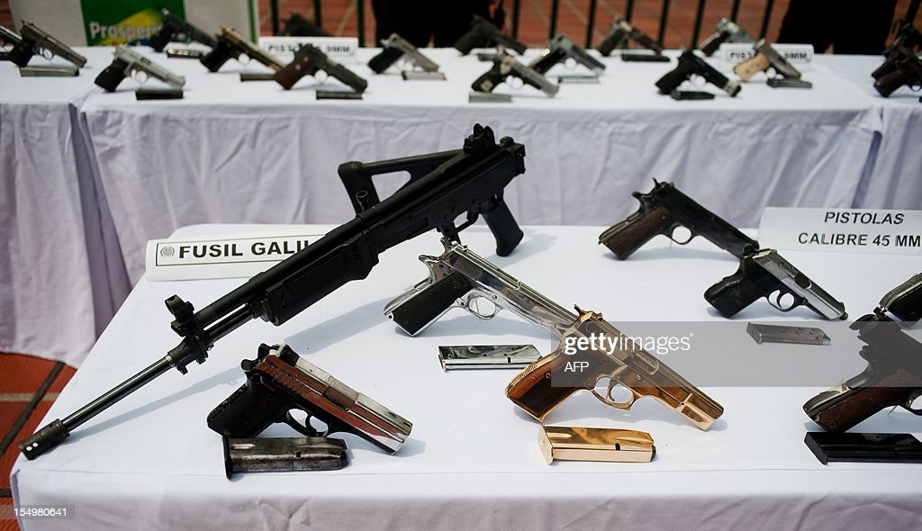 Picture of some of the weapons seized to a criminal gang, being displayed during a press conference in Cali, department of Valle del Cauca, Colombia, on October 29, 2012. The National Police confiscated 49 pistols, 18 revolvers, two rifles and 51 magazines during Operation 'Vulcano 3' against criminal gangs. According to official information, these weapons belonged to the criminal gang 'Los Rastrojos'. AFP PHOTO/Luis ROBAYO
