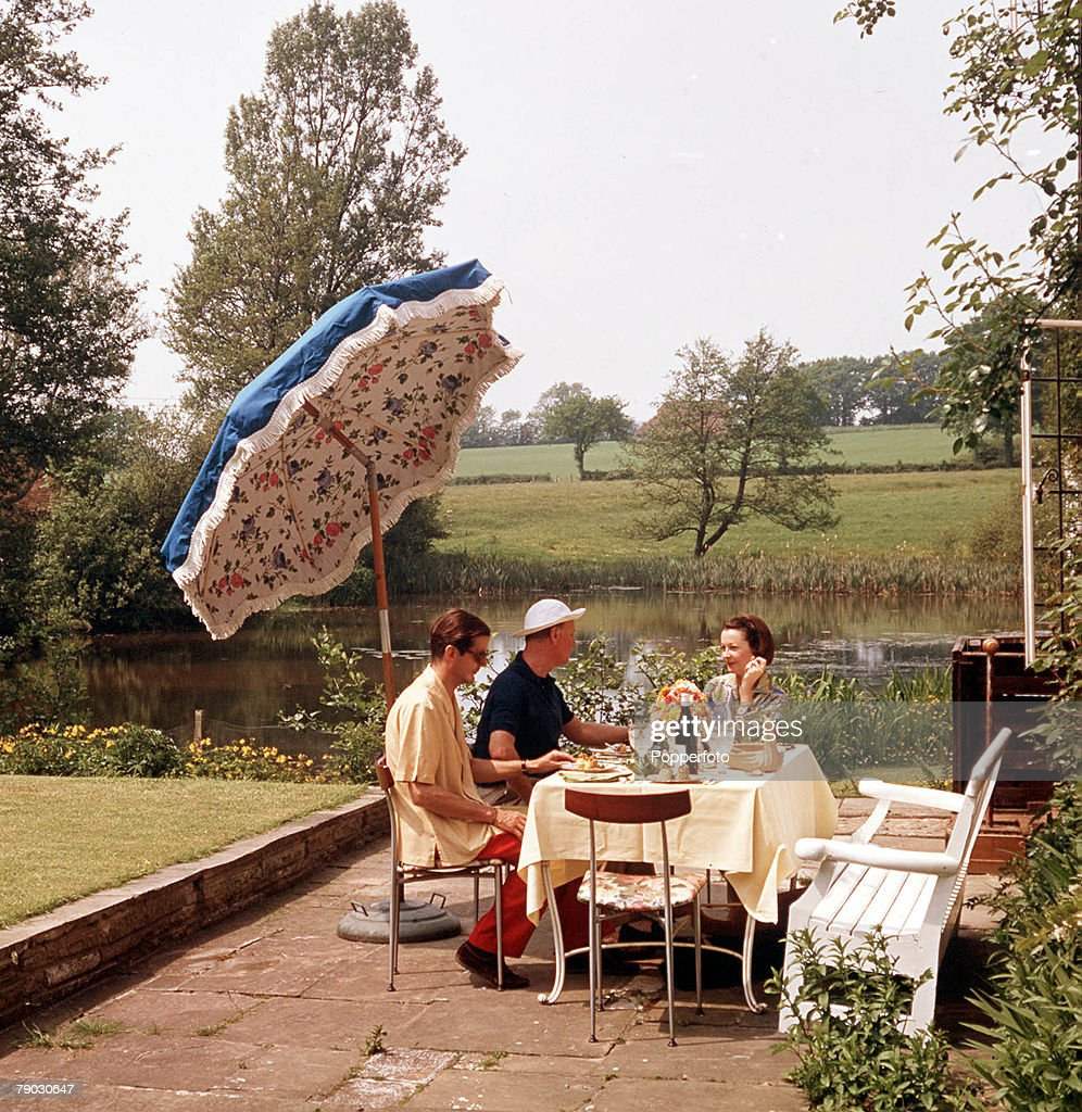 A picture of the American actress Vivien Leigh relaxing with friends outside at a table with a scenic garden area