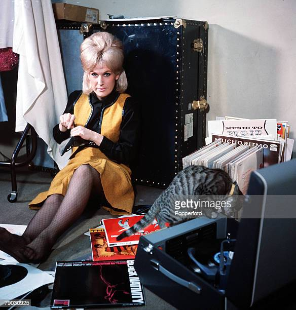 A picture of the British singer Dusty Springfield sitting with her cat amongst her record collection