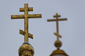 Picture of the christian church with golden dome and Cross on the top close up. Golden dome and Cross on the top against background of gray sky.