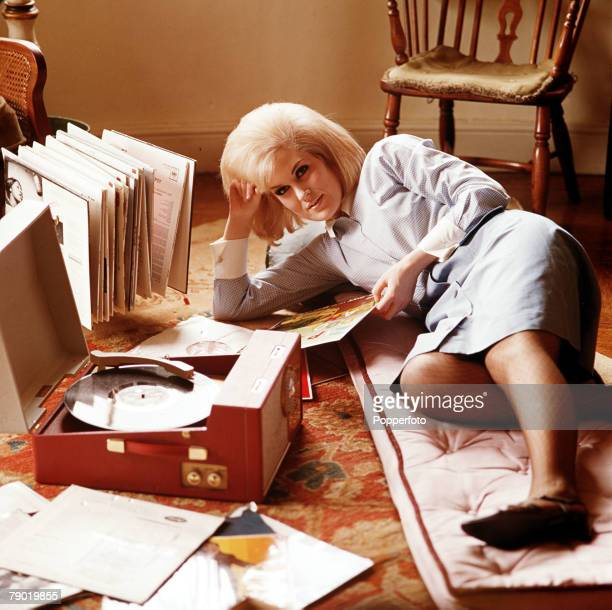 1965 A picture of the famous British singer Dusty Springfield lying on the living room floor at home listening to her LPs on a record player whilst...