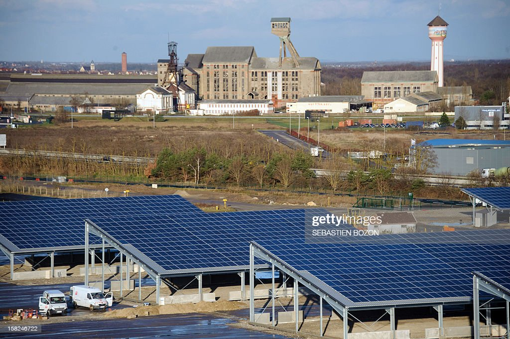 Picture of the panels of Ungersheim's solar power plant with an old potash mine in the background taken on December 6, 2012 in Ungersheim, eastern France.