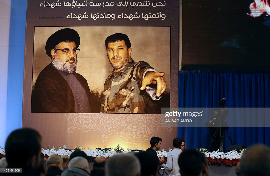 A picture of the the Shiite Hezbollah movement chief Hassan Nasrallah (L) and Hassan Hawlo al-Lakiss (R) a top member of the movement who was murdered on December 4, is seen as Nasrallah gives a televised speech in Beirut on December 20, 2013. Nasrallah warned that his Lebanese Shiite movement will 'punish' Israel for the killing of a top leader earlier this month.