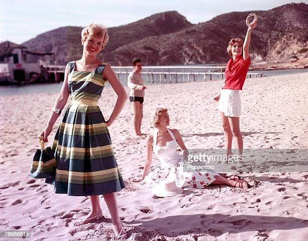 1959 A picture of three fashionable young woman at the seaside on the beach playing catch the hoop whilst relaxing in the sun