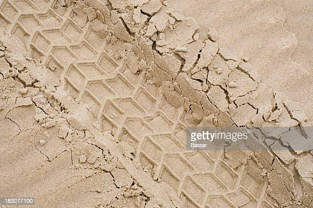 A picture of tire tracks in the sand