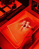 Picture of two girls (9-12) being developed in darkroom (Composite)