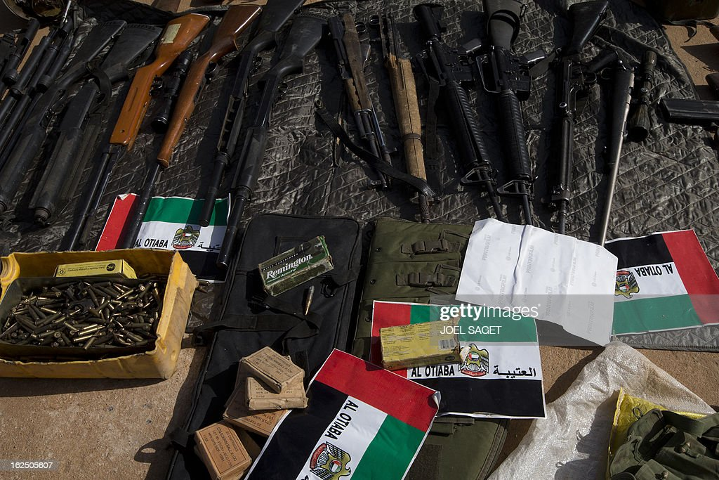 A picture of weapons and ammunitions seized from Islamist fighters exhibited with flags from the United Arab Emirates by the Malian army in the centre of Gao on February 24, 2013. Tuareg militias battled Arab rebels in northern Mali Saturday, while French jets, US drones and Chad's elite desert forces were also in action in a major push to stamp out resistance from pockets of Islamist fighters. After recapturing the north's cities from the Al Qaeda groups that had controlled them since April 2012, the six-week-old French-led offensive took the fight to the retreating Islamist insurgents' toughest desert bastions.