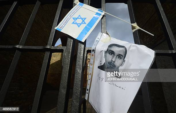 A picture of Yosi Damari a 22 yearold man from Israel who was found beaten to death and an Israeli flag hang at a gate at the ruins of the downtown...