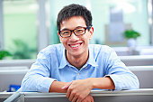 picture of young happy asian man in office