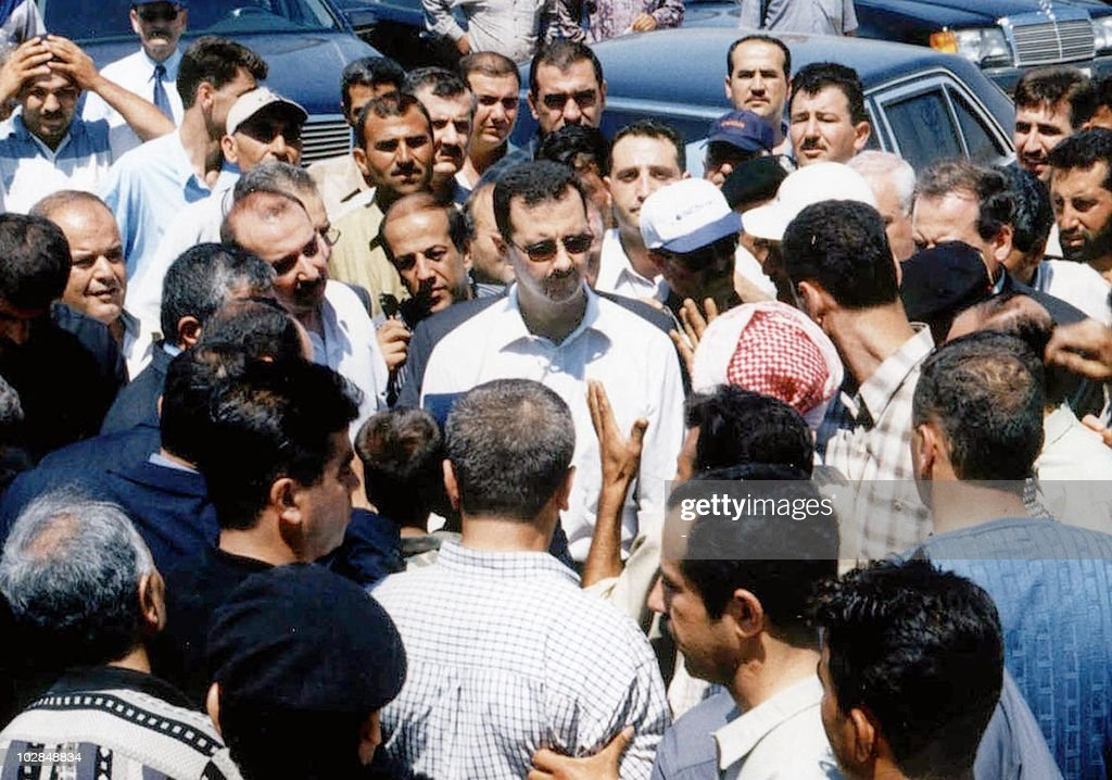 Picture received by AFP 19 June 2002 shows Syrian President <a gi-track='captionPersonalityLinkClicked' href=/galleries/search?phrase=Bashar+al-Assad&family=editorial&specificpeople=206274 ng-click='$event.stopPropagation()'>Bashar al-Assad</a> (C) during a tour on 16 June of the village of Zeyzoun in the northern Syrian province of Hama where a dam collapsed early this month. The Zeyzoun dam collapse, which had disastrous consequences for the local population, killed 22 people, left some 4,000 homeless and destroyed around 18,000 hectares (44,000 acres) of cultivated land, a blow to the country's important farming sector.
