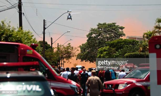 TOPSHOT Picture released by Brazilian newspaper O Popular showing a helicopter arriving at the scene of a shooting at the Goyases private school in...