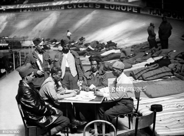 Picture released on April 21 1945 of repatriated war prisoners waiting for their departure by playing cards at the Velodrome d'Hiver at the end of...