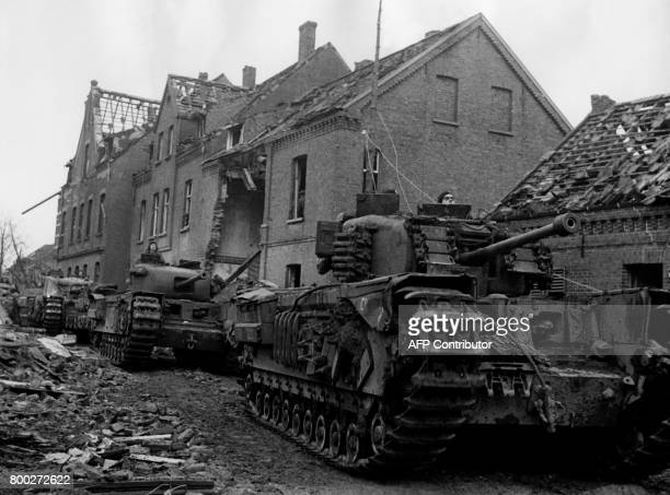 Picture released on February 11 1945 of British troops riding through wrecked streets of Cleves after bombings during the Second World War / AFP...