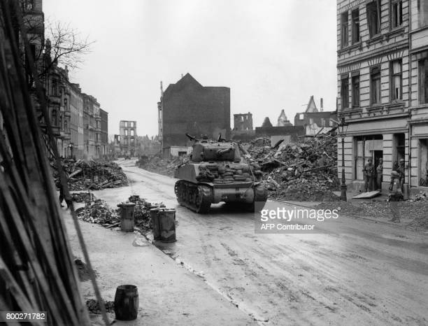 Picture released on February 1945 of an American tank riding through a wreckedlined street in Cologne after bombings on the key Rhine city during the...