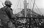 A picture released on May 05 1975 shows an GI watching South Vietnamese refugees crowding a US Navy boat off the coasts of Vietnam at the end of...