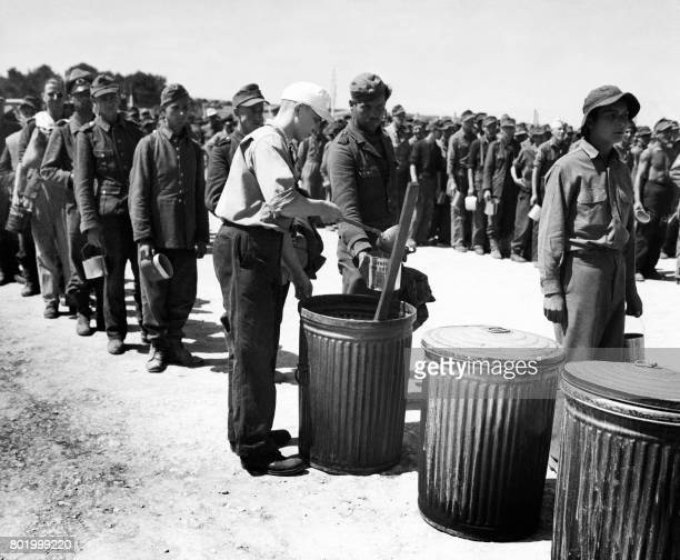 Picture released on May 28 1944 showing German prisoners queuing for a ration of food at compound at Delta base continental central prisoner of war...