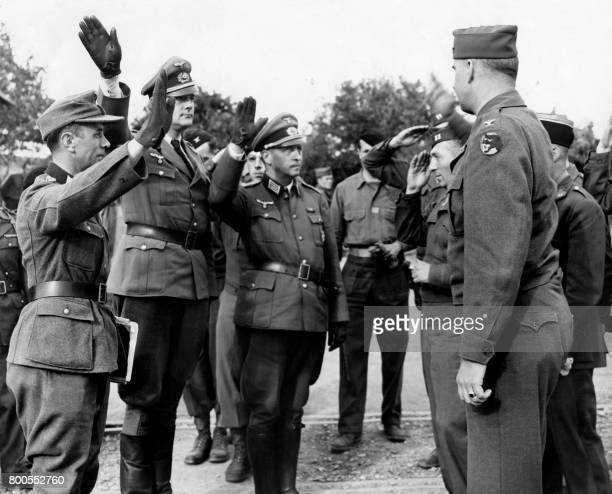 Picture released on May 9 1945 of German defeated Nazis rending their last party salutes at the headquarters 66th infantry division before...