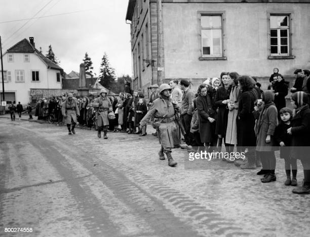 Picture released on November 25 1944 of civilians of Lutzelhouse lining edge of the streets as American soldiers advance through the town during the...