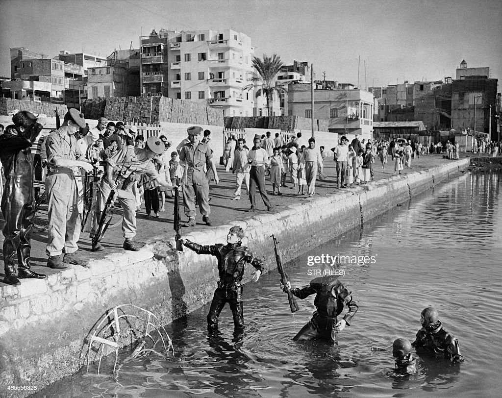 Picture released on November 26 1956 of British divers resurfacing arms from the industrial basin of the Suez Canal in Port Saïd in Egypt after the...